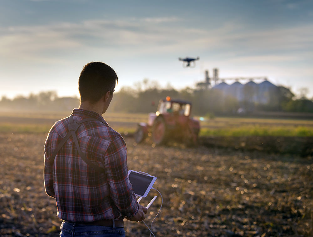 Drone being used on farmland showing how the commercial drone industry is changing agricultural practices